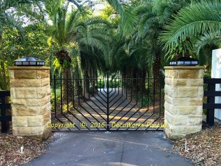 Custom pillar lights and stainless steel entrance gates with Art Deco palm leaf motif